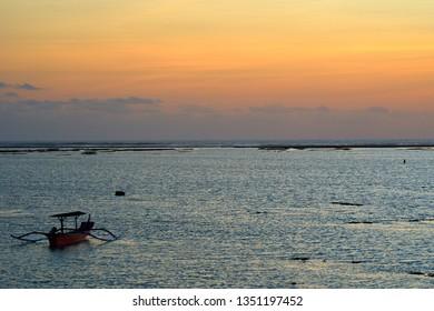 KUTA, BALI ISLAND, INDONESIA - SEPTEMBER 13, 2018: Traditional Balinese boats - trimarans - in the ocean.