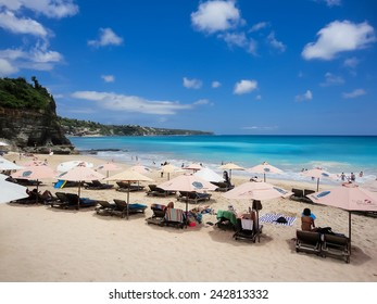 KUTA, INDONESIA - AUGUST 20, 2013: Unidentified tourists at Dreamland beach at Bali. Dreamland Beach is a beautiful panoramic coral beach appointed as best surfing point in Bali.