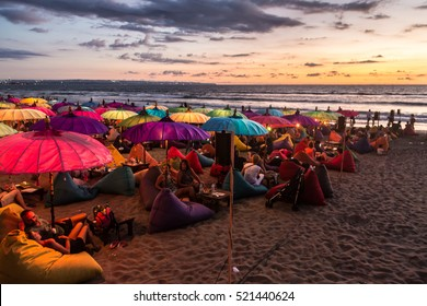 KUTA, INDONESIA - FEBRUARY 19, 2016: A large crowd of tourists enjoy the sunset at a bar on Kuta beach in Seminyak, Bali. The island is famous for its nightlife.