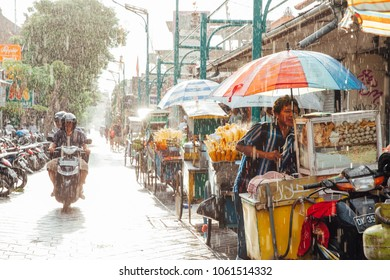 Kuta, Indonesia - March 08, 2016: Indonesian food vendor hides from the rain under umbrella of his stall on the street of Kuta, Bali, Indonesia on March 08, 2016