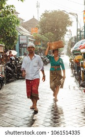 Kuta, Indonesia - March 08, 2016: Indonesian man and woman in traditional clothes walking under the rain on the street of Kuta, Bali, Indonesia on March 08, 2016