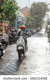Kuta, Indonesia - March 08, 2016: Indonesian man riding a motorbike under the rain on the street of Kuta, Bali, Indonesia on March 08, 2016