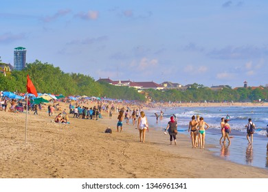 KUTA, INDONESIA - SEPTEMBER 5, 2018: Tourists and locals on famous Kuta beach in Seminyak, Bali. This is the perfect place for learning surfing.