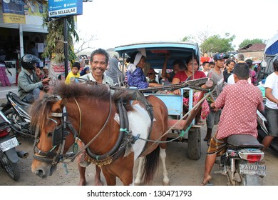 KUTA LOMBOK, INDONESIA - JULY 22 : Unidentified Indonesian women using transport by horse and chariot to the bustly traditional food market of Kuta Lombok on July 22 2012.