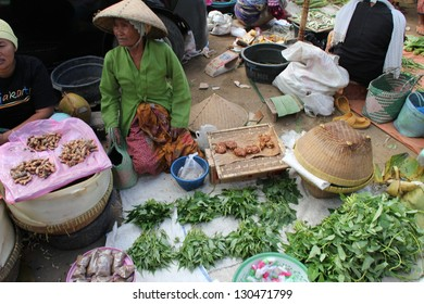 KUTA LOMBOK, INDONESIA - JULY 22 : A woman is selling produce to local customers at Kuta Lombok's sunday food market on July 22 2012. The traditional market attracts many from around Kuta Lombok.