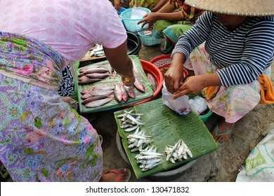 KUTA LOMBOK, INDONESIA - JULY 22 : A woman is selling fish to local customers at Kuta Lombok's sunday food market on July 22 2012. The traditional market attracts many from around Kuta Lombok.