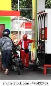 Kuta/Bali - September 12, 2016: Petrol attendant filling up motorcycle from a pertamina fueling station in Bali