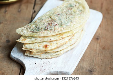 Kutabs or Gozleme - herbs or meat stuffed flatbreads on a wooden rustic background. Azerbaijani traditional cuisine. Vegan food.