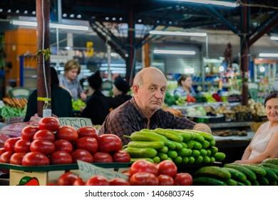 Kutaisi / Georgia - 05.21.2019: Georgian street market. Elderly georgian man street vendor sells local products and vegetables