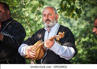 KUTAISI/GEORGIA - JUNE 19, 2016: Georgian aged man playing panduri and singing traditional georgian songs
