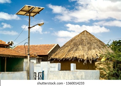 Kutch ,30 August,2005: Progressive village having  Solar Panel  for street lighting at night  with straw huts and tiled houses in background ,Kutch, Gujarat, India, Asia