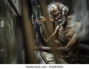 Kuthampully, Ottapalam, Kerala, India - 3rd January 2019 - Unknown old-man operating handloom at his home.