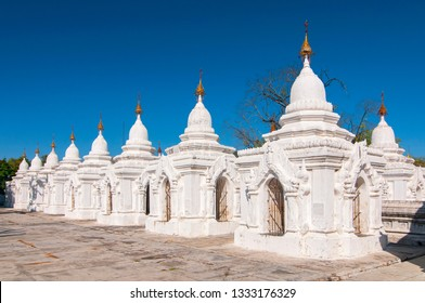 Kuthodaw Pagoda contains the worlds biggest book. There are 729 white stupas with caves with a marble slab inside page with buddhist inscription. Mandalay, Myanmar.