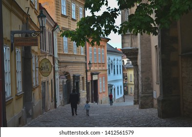 Kutna Hora / Czech Republic - May 18 2019: A father and a child at dusk, walking down a medieval street of historic town Kutna Hora