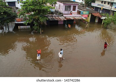 KUTTANAD, INDIA - JUNE 26:Unidentified people walk on the flood water on June 26,2013 in Kuttanad, India. Kuttanad is an area below sea level and is often affected by flood during heavy rains