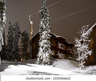 Kuusamo / Finland - February 2019: Aurinko Rinne wooden apartment houses at the edge of the illuminated Talvijarvi T-bar lift and slope in Ruka on a cold February evening