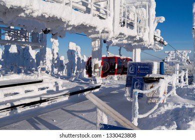 Kuusamo / Finland - February 2019: The red gondolas from Ruka Valley arrive at the Saarua Top station in the Ruka ski area on a beautiful and sunny winter day