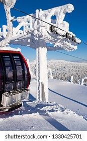 Kuusamo / Finland - February 2019: A red gondola leaves the Saarua Top station in the Ruka ski area on a beautiful and sunny winter day