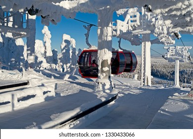 Kuusamo / Finland - February 2019: Three red gondolas from Ruka Valley arrive at the Saarua Top station in the Ruka ski area on a beautiful and sunny winter day