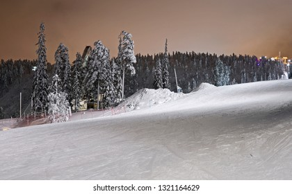 Kuusamo / Finland: View from the illuminated Talvijarvi slope to the ski jumping hill in Ruka on a mystic evening in February