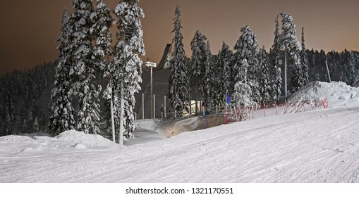 Kuusamo / Finland: View from the illuminated Talvijarvi slope to the large ski jumping hill in Ruka on a mystic evening in February