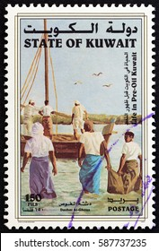 "KUWAIT - CIRCA 1998: A stamp printed in Kuwait from the ""Life in Pre-Oil Kuwait"" issue shows pearl divers wading out to boat, circa 1998."