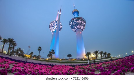 KUWAIT - CIRCA MARCH 2017: The Kuwait Towers day to night transition illuminated at night - the best known landmark of Kuwait City. Kuwait, Middle East. View with palms and flowers at foggy