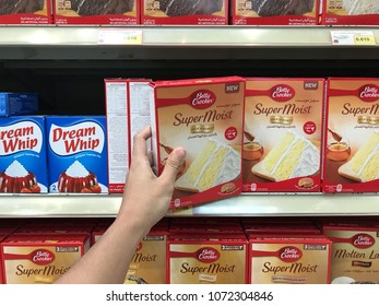 KUWAIT CITY, KUWAIT - April 25, 2017 : A hand picking up Betty Crocker brand of cake mixture that lined up on shelves in the market. Baking cake for preparation of having it on Eid Mubarak.