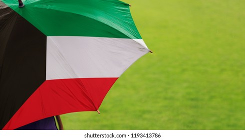 Kuwait flag umbrella. Close up of printed umbrella over green grass lawn /field. Rainy weather forecast concept.