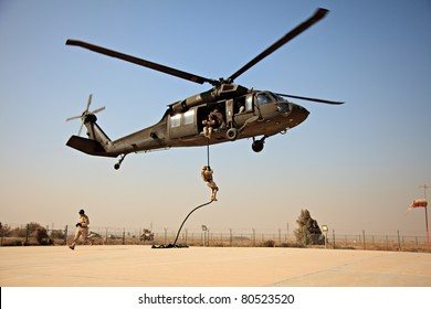 KUWAIT - JANUARY 19: U.S. Navy EODs fast ropes down a Blackhawk SH-60 for a training exercise January 19, 2011 in Kuwait.