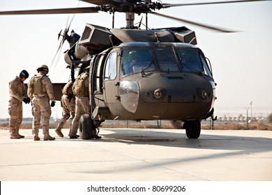 KUWAIT - JANUARY 19: U.S. Navy EOD boards a Blackhawk SH-60 for a training exercise on January 19, 2011 in Kuwait.  Chief Petty Officer Michael Solis prepares his team to fast rope down the Blackhawk.