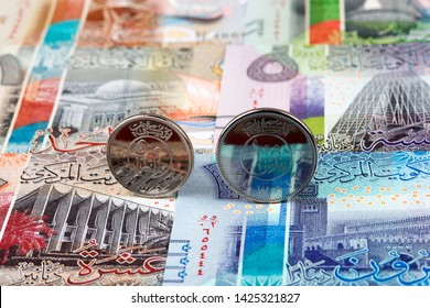 Kuwaiti dinar coins on the background of banknotes