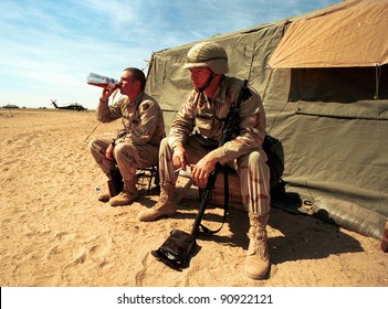 KUWAIT-IRAQ BORDER - FEBRUARY 22: Two United States Army soldiers enjoy a bit of a rest between military exercises just south of the Iraqi border in Kuwait  on Feb 22, 1998 on the Kuwait-Iraq border.