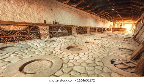 KVARELI, GEORGIA - OCT 3: Cellar, aged bottles and qvevri, earthenware vessels in ground of Kindzmarauli Corporation Wine House on October 3, 2016. Winery produces 25 varieties of wine and 10 brandies