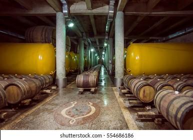 KVARELI, GEORGIA - OCT 3: Wooden barrels and metal cistern with wine inside old cellar of Kindzmarauli Corporation Wine House on October 3, 2016. Winery produces 25 varieties of wine and 10 brandies
