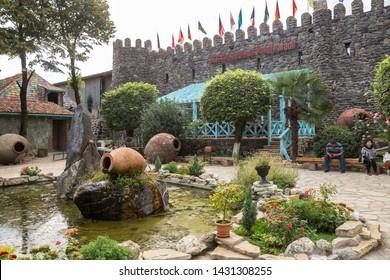 KVARELI, GEORGIA - OCTOBER 01, 2018: Courtyard yard of the plant Kindzmarauli Corporation is decorated with large clay tanks for making wine - kvevri