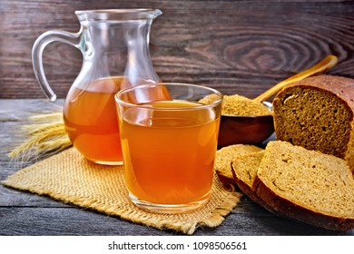 Kvass in glassful and glass jug on burlap, malt in a bowl, rye bread on wooden plank background