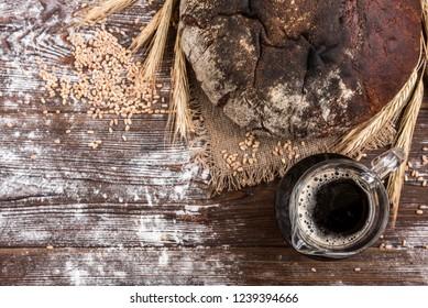 Kvass with rye bread on dark wooden background.