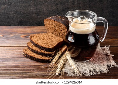 Kvass with rye bread on wooden background.