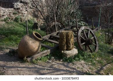 Kvevri at narikala fortress with an old wooden wheel