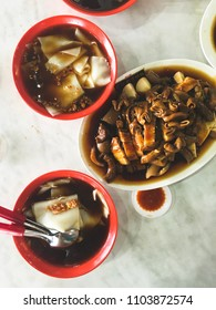 Kwan Chap (??; gu? zh?), a Teochew dish of flat rice sheets in dark soy sauce soup, served with pig offal, braised duck meat, beancurd, preserved salted vegetables, and braised hard-boiled eggs.