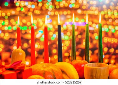 Kwanzaa celebration concept with seven candles red, black and green, gift box, pumpkin, bowl and fruit on light blur bokeh background, close up