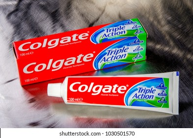 KWIDZYN, POLAND – FEBRUARY 19, 2018: Colgate triple action toothpaste isolated on metal background. Colgate is manufactured by American consumer-goods conglomerate Colgate-Palmolive.