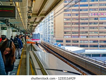 Kwun Tong, Hong Kong - February 9, 2016: Passengers are waiting on the platform for the Green Line MTR train entering Kwun Tong Station.