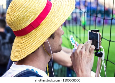 KYIV, UKRAINE—MAY 26, 2018: UEFA Champions League in Kiev Finale Young man looking at stadium taking pictures of soccer match training standing behind football field fence for protect ball in fan zone