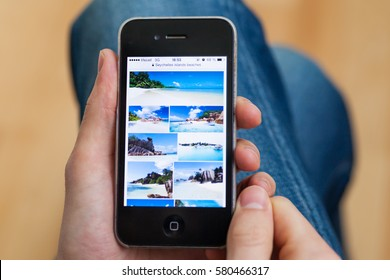 Kyiv - February11:Hand holding iPhone with Seychelles images in Google Search on the display.Vacation Planning.Ukraine,February 11,2017. In processing image applied only cropping and color adjustments