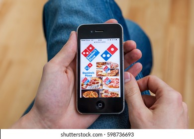 Kyiv - February11:Male hand holding iPhone with Domino's pizza delivery images in Google search on the display. Ukraine,February11,2017. In processing image applied only cropping and color adjustments