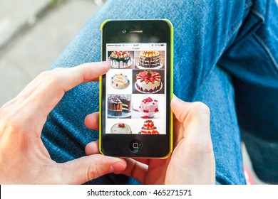 Kyiv - May 06: Male hand holding Apple iPhone with cakes images in Google Search on the display, May 06, 2016, Kyiv, Ukraine