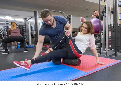 Kyiv UA, 28-03-2019. Mature woman doing sport exercises with personal trainer at gym. Male instructor assisting older woman.