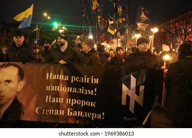 Kyiv, Ukraine - 01.01.2021: Night political rally of Ukrainian nationalists. Stepan Bandera birthday. Column of activists walking with fires on the city street. Reportage editorial photo.